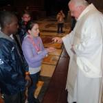 Don Bandirali durante la professione di fede all'altare della Cattedra in S. Pietro, mentre consegna il cero ai ragazzi.